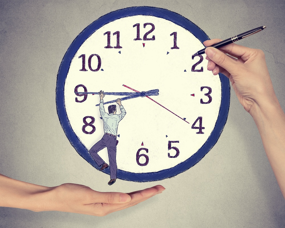 Business man trying to stop time. Man hanging on clock arrow isolated on gray office wall background. Time pressure passing past concept.jpeg