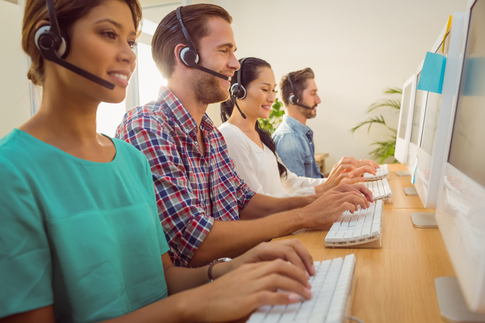 Business team working together at a call centre wearing headsets-1